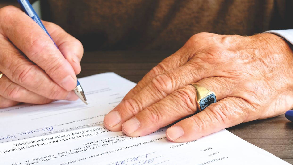 hands while signing a document
