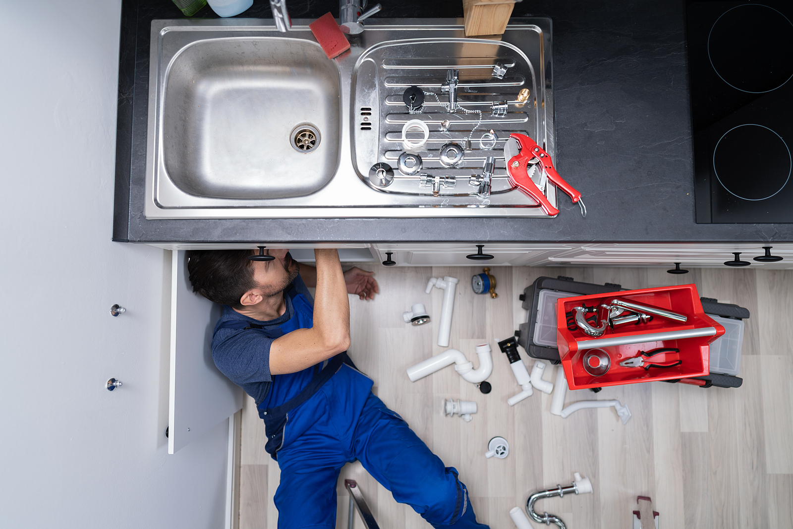 Plumber fixing a sink leakage