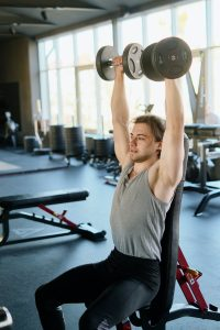 a guy sitting while using a weight bench