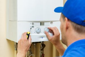 Hot water plumber setting up central gas heating boiler at home